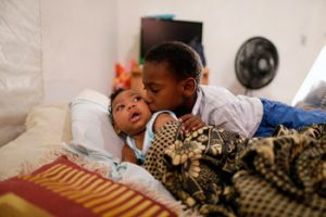 "Danilo, from Pernambuco, Brazil, is being hugged by his brother. Danilo, who has microcephaly, visits the hospital twice a week. His mother, Ana Paula, says ""With all this family love, it is easier to take care of him."" Photo: Ueslei Marcelino/UNICEF"